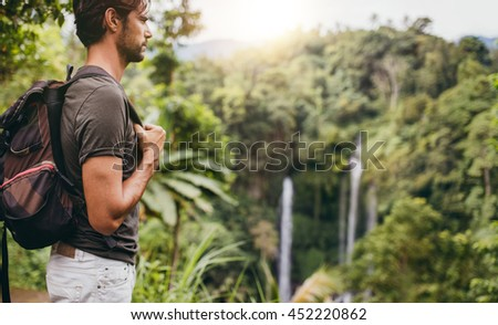 Side view shot of young man with backpack hiking in nature. Male hiker near waterfall in forest.