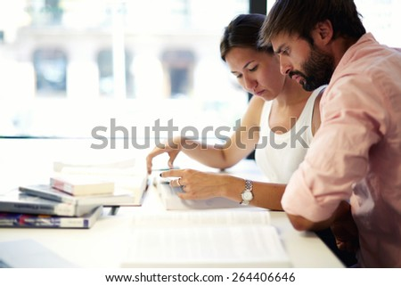 Side view shot with two young students learn together in modern library, couple of university students focused read book while preparing for exams, teenagers sit at the desk with open books - stock photo