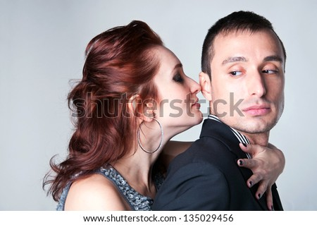Side view studio portrait of young beautiful passionate couple a man and a woman embracing each other, standing close, feeling desire and temptation. Gray background - stock photo