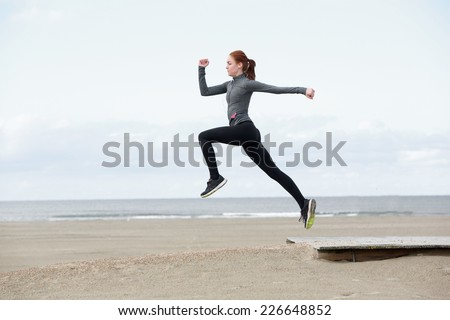 Side view young female runner jumping outdoors