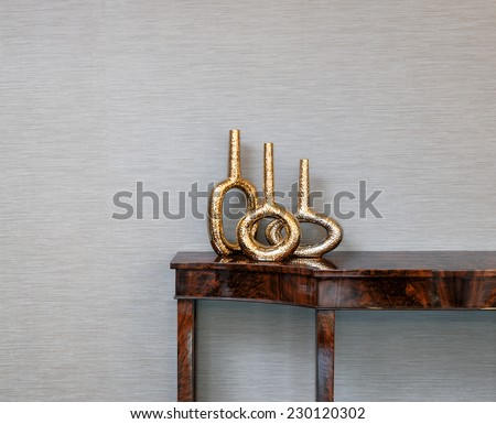 Sideboard in front of a grey wall with art objects - stock photo