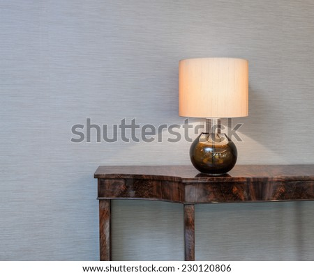 Sideboard in front of a grey wall with table lamp
