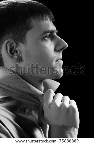 sideview headshot portrait of young handsome brunet guy in gray shirt checking collar on green