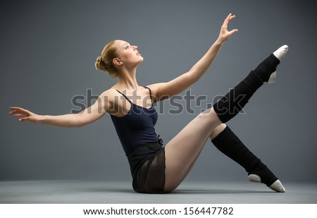 Sideview of dancing on the floor ballerina with her leg up, isolated on white on grey. Concept of elegant art and sportive hobby - stock photo