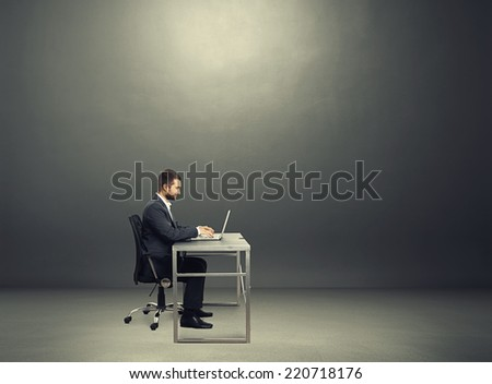 sideview of smiley young businessman sitting at the table and working with laptop in the dark room with empty copyspace - stock photo