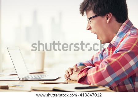 Sideview of young yawning man sitting at office desk with blank laptop and other items - stock photo