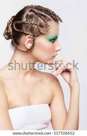 sideview portrait of beautiful young dark blonde woman with creative braid hairdo posing on gray