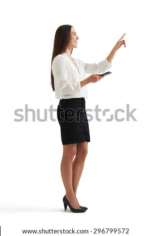 sideview portrait of businesswoman in formal wear holding smartphone and pointing at something. isolated on white background - stock photo