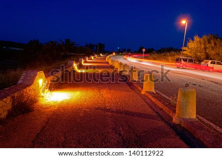 sidewalk by night with light trails on the road - stock photo