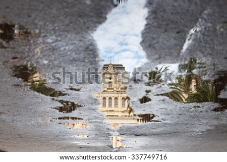Sidewalk with puddles of water and mirroring image - stock photo