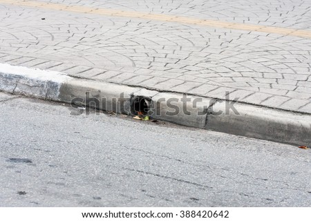 Sidewalk with yellow mark and street with gutter pipe - stock photo