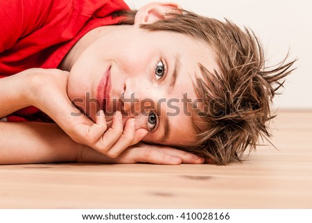 Sideways close up on head of happy boy in red shirt lying on hardwood floor with hands near face