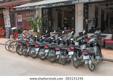 SIEM REAP, CAMBODIA - 23 DEC 2013: Cafe with many motorcycles parked along the pavement, tables and chairs - stock photo
