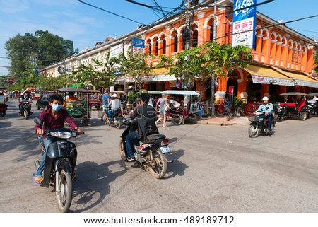 SIEM REAP, CAMBODIA - 23 DEC 2013: Many motorcycles and people on a popular tourist street in the town center with building in vibrant color.