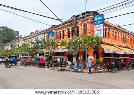 SIEM REAP, CAMBODIA - 23 DEC 2013: Tourist areas on busy corner intersection with French colonial architecture a Mexican restaurant and Tuk tuk taxi.