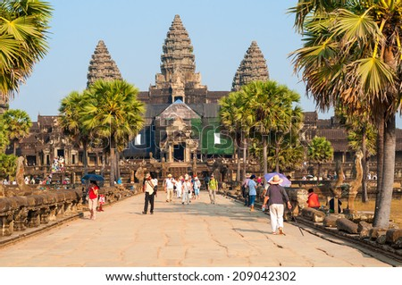 SIEM REAP, CAMBODIA - FEBRUARY 17, 2014: The main temple of Angkor Wat, seen from the causeway on the western approach, draws thousands of visitors from all over the world. - stock photo