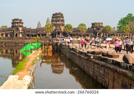 SIEM REAP, CAMBODIA - FEBRUARY 18, 2014: Throngs of visitors cross the moat that surrounds the temple complex of Angkor Wat. Just beyond is the west perimeter gallery, with the main shrine farther in. - stock photo