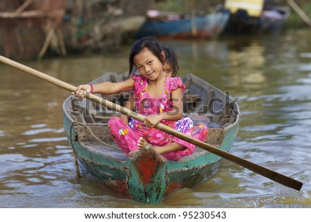SIEM REAP, CAMBODIA - JAN 23: Two children rowing rowing boat on Tonle Sap Lake in Siem Reap, Cambodia on January 23, 2012. Tonle Sap is the largest freshwater lake in SE Asia peaking at 16k km2. - stock photo