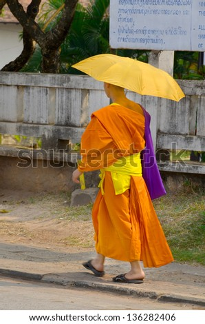 SIEM REAP, CAMBODIA - MARCH 27: A monk walking with sun umbrella in Siem Reap, Cambodia on March 27, 2013. Buddhism is currently estimated to be the faith of 96% of the Cambodian population.