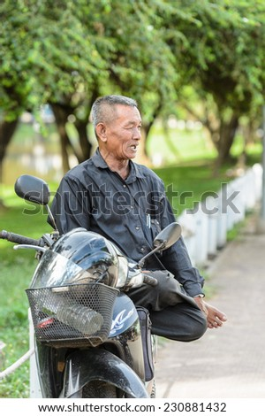 SIEM RIEP, CAMBODIA - SEP 28, 2014: Unidentified Khmer man sits on his motorbike in Siem Reap. 90% of Cambodian people belong to Khmer etnic group