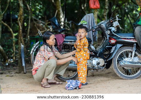 SIEM RIEP, CAMBODIA - SEP 28, 2014: Unidentified Khmer woman and her little son in Siem Reap. 90% of Cambodian people belong to Khmer etnic group