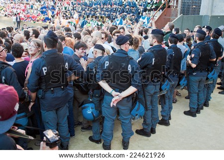 "SIENA, ITALY - AUGUST 16: Police keep order before start of annual traditional Palio di Siena horse race in medieval square ""Piazza del Campo"" August 16, 2014 in Siena, Italy"
