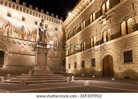 SIENA, ITALY - MAY 14, 2009: Sallustio Bandini on Piazza Salimbeni at night, Siena, Tuscany, Italy. Salimbeni palace headquarters of Banca Monte dei Paschi di Siena - the oldest bank in the world. - stock photo