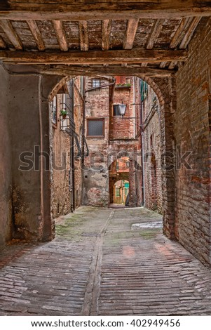 Siena, Tuscany, Italy : old narrow alley with underpass and arches in the historic city center
