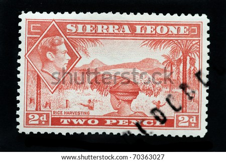SIERRA LEONE - CIRCA 1940 - Postage stamp showing native of country rice harvesting and inset of King George 6th circa 1940