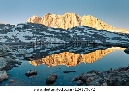Sierra Nevada Alpenglow Reflection - Mount Hitchcock mirrors in a lake at sunrise. - stock photo