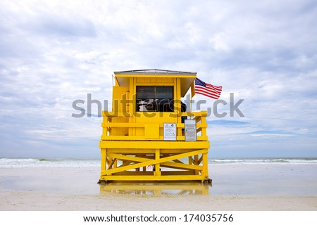 Siesta Key Beach, Florida USA, yellow lifeguard house on with American flag a beautiful summer day with ocean and blue cloudy sky  - stock photo