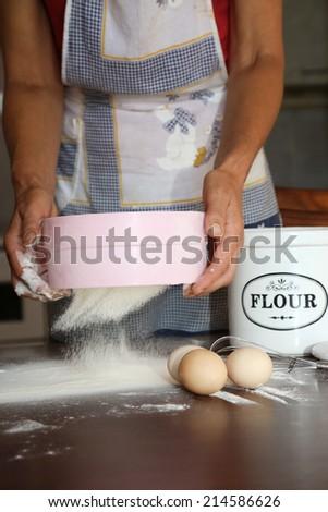 Sieve flour, A baker sieve flour to make his bread - stock photo