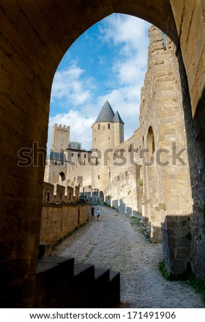 Sight of towers at Carcassonne castle medieval city through arc in France - stock photo