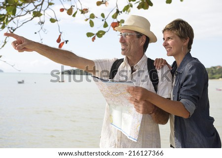 Sightseeing: Middle aged couple on vacation search the way with map - stock photo