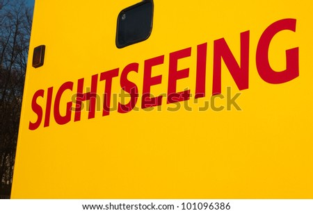 Sightseeing writing on Yellow Tourist Tour Bus in Red Text - stock photo