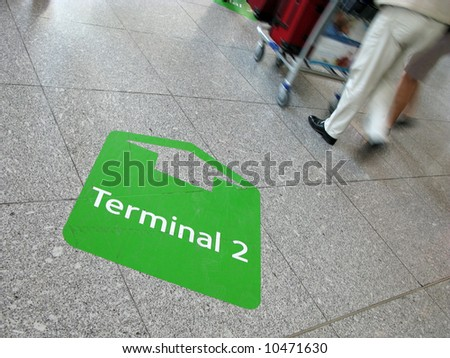 Sign arrow to terminal on the floor in airport with people on a journey - stock photo
