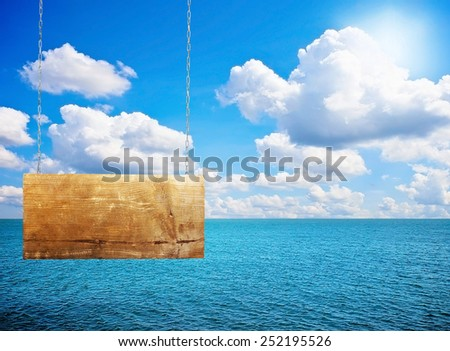 Sign board on chain near the sea in sunlight - stock photo