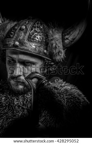Sign, Costume, Viking warrior with a huge sword and helmet with horns - stock photo