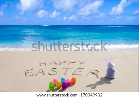 "Sign ""Happy Easter"" with bunny and color eggs on the sandy beach by the ocean - stock photo"
