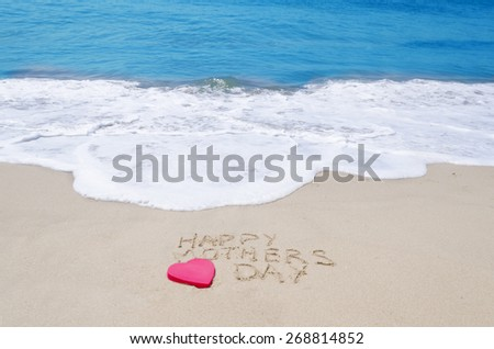 """Sign """"Happy mothers day"""" on the sandy beach next to ocean - stock photo"""