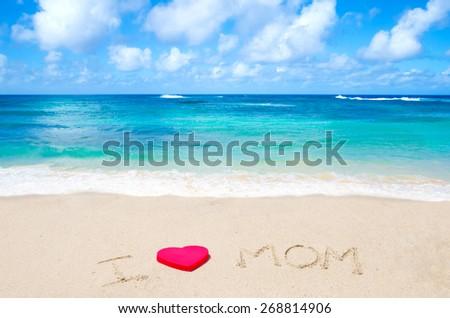 "Sign ""I love mom"" on the sandy beach next to ocean - stock photo"