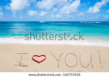 """Sign """"I love you"""" with heart on the sandy beach by the ocean - stock photo"""