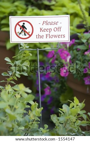 Sign in garden near sidewalk - stock photo