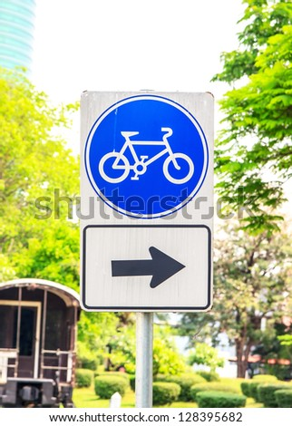 Sign is way for bicycle in garden