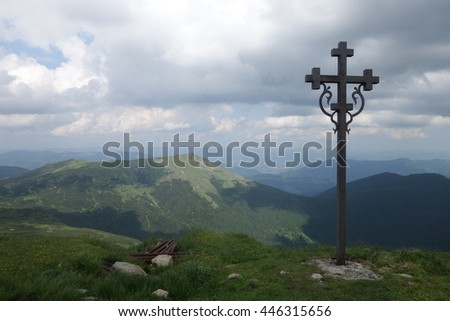 Sign of faith. Iron cross in a cloudy sky. Mount Pop Ivan, Transcarpathia - stock photo