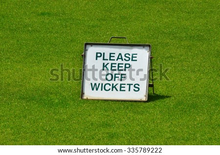 "Sign on green grass reads: ""Please keep out off wickets"". - stock photo"