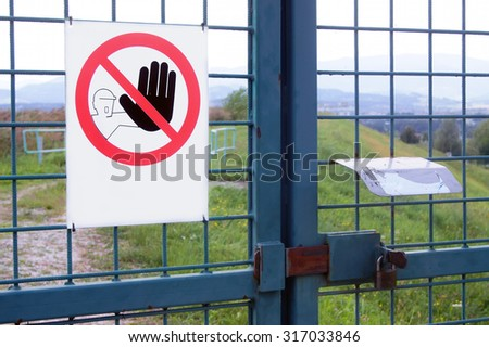 Sign on iron fence with a door lock - stock photo