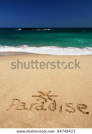 "Sign ""Paradise"" and drawing of the sun written in the sand of the tropical beach of Sri Lanka near the azure sea - stock photo"