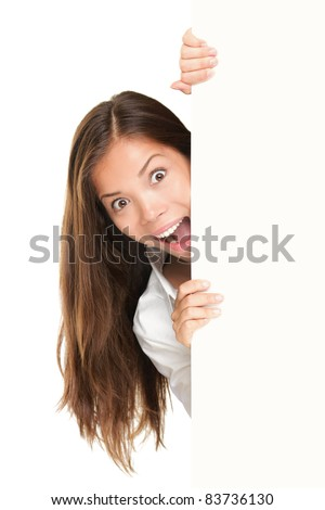 Sign people - woman peeking out from behind billboard paper poster. Excited woman looking surprised. Beautiful brunette with long hair. Asian Caucasian female model isolated on white background - stock photo