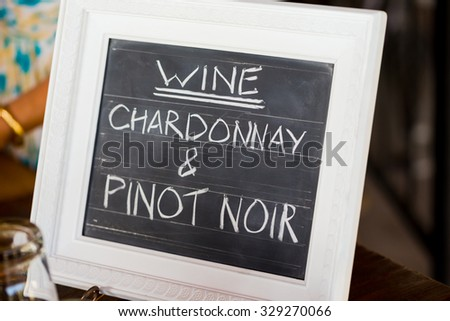 Sign showing the wine menu at a wedding recepiton in Southern Oregon includes chardonnay and pinot noir.